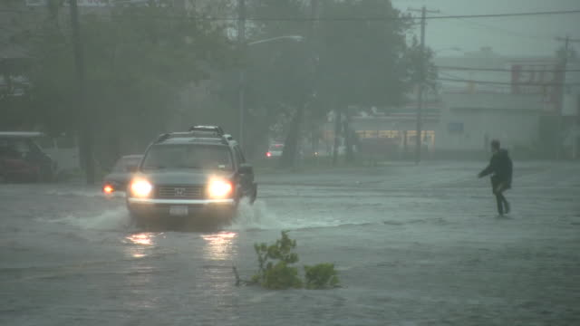 fast moving flood waters inundate austin blvd in island park ny as both pedestrians and motorists attempt to navigate flooded streets - storm surge stock videos & royalty-free footage