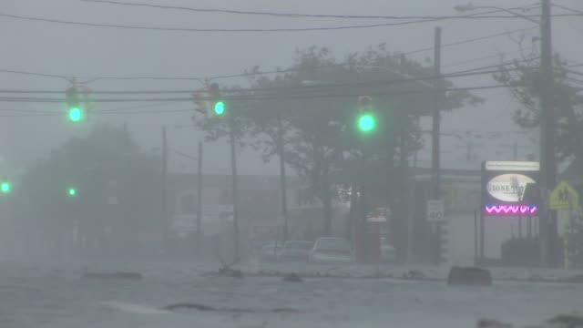 fast moving flood waters race across a city street, as strong winds blow trees and traffic lights during hurricane irene in 2011. - hurricane irene stock videos & royalty-free footage