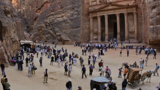 T/L, LS, fast moving people outside the Al Khazneh (Treasury) at ancient stone city of Petra / Jordan