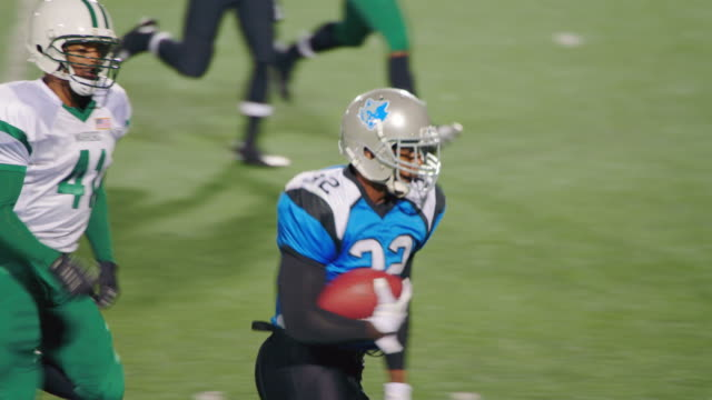 ms slo mo. fast running back carries football into end zone for touchdown and celebrates with teammates. - タッチダウン点の映像素材/bロール