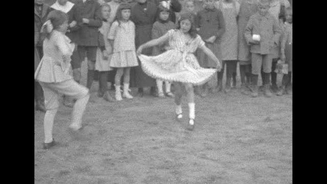 [fast] scores of seated children being entertained by a couple of young dancers // the children applaud and are treated to cups of hot chocolate a... - erster weltkrieg stock-videos und b-roll-filmmaterial