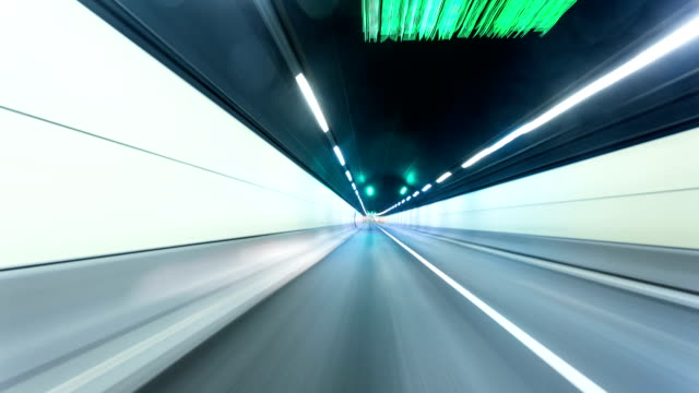 Fast traffic in tunnel of modern city, time lapse.