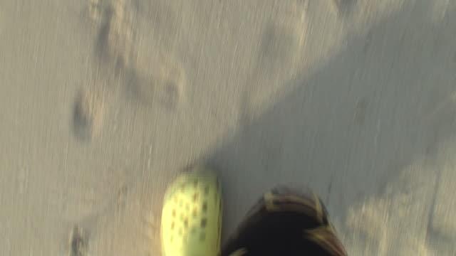 vidéos et rushes de en marchant le long de la plage; gros plan sur les pieds - membres du corps humain
