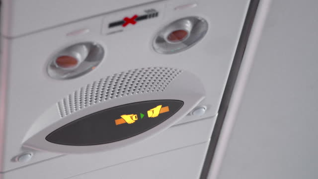 4k fasten your seat belt sign disappear on airplane - safety stock videos & royalty-free footage