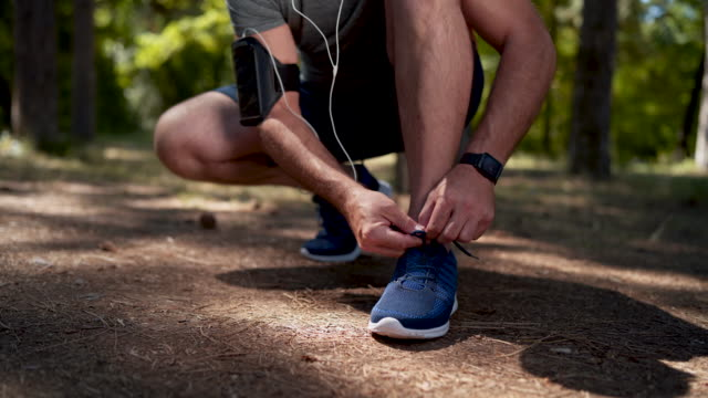 vídeos de stock e filmes b-roll de fastening those laces for better run - one mature man only