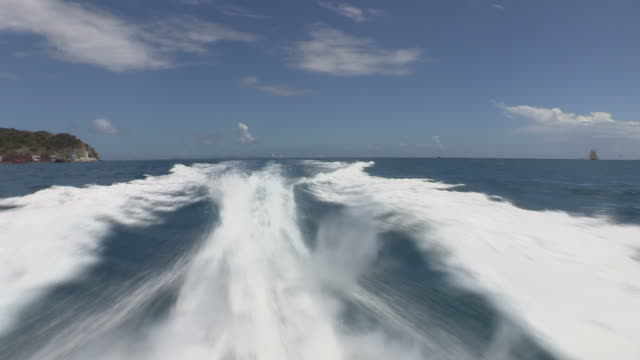 a fast-moving powerboat creates a wake in the ocean during the st. maarten heineken regatta. - speed boat stock videos & royalty-free footage