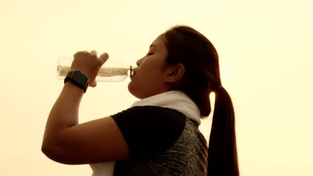 脂肪アジアの女性は、実行後に水を飲む.healtyコンセプト。 - ウォーターボトル点の映像素材/bロール