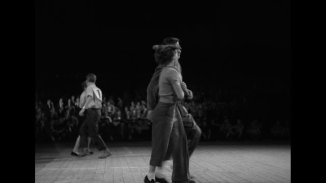 vidéos et rushes de fat bandleader enthusiastically dances with woman in shiny skirt; couples doing athletic jitterbug; winning couple with flowers and the bandleader... - rock