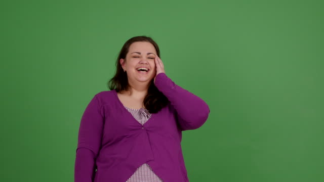 A fat girl laughs joyfully on a green background