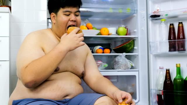 vídeos y material grabado en eventos de stock de hombre gordo está sentado al lado de la nevera y está durmiendo. - hambriento