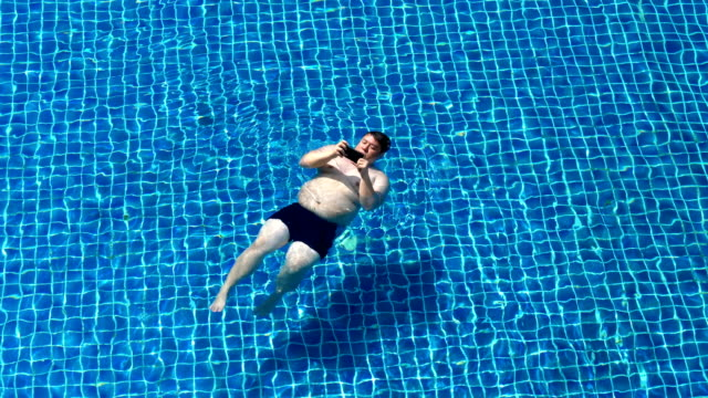 fat man lying on the water while using phone - reclining stock videos & royalty-free footage