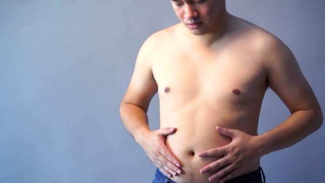 デブ男の手持ち株脂肪腹、分離の背景、灰色の背景色に太りすぎ。 - 腹点の映像素材/bロール