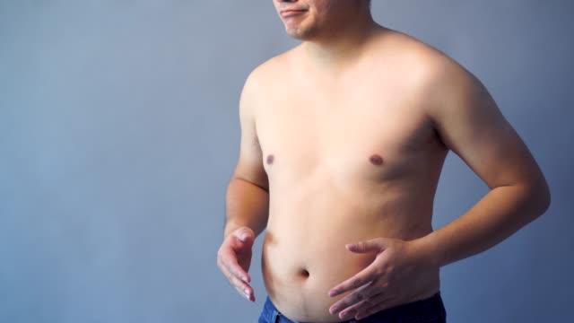 vídeos y material grabado en eventos de stock de hombre gordo con sobrepeso con mano holding grasa vientre, en el fondo aislante, color gris telón de fondo. - piel grasa