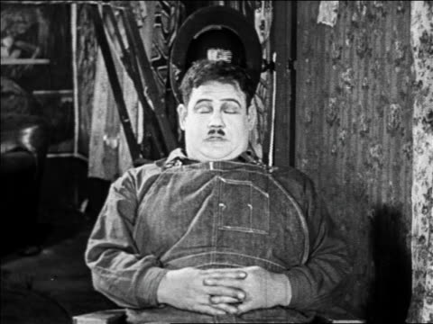 b/w 1925 fat man sitting in chair snoring as hat bobs up down / feature - oliver hardy stock videos & royalty-free footage