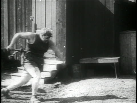 b/w 1914 fat man (fatty arbuckle) tied by offscreen rope pulling rope + walking / feature - pulling stock videos & royalty-free footage