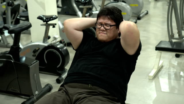 Fat Man tying to Sit Ups in Gym