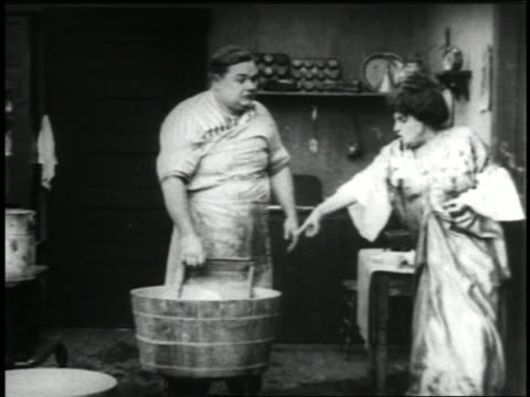 vídeos y material grabado en eventos de stock de b/w 1915 fat man (fatty arbuckle) washing clothing in bucket + arguing with wife (alice davenport?) - tarea doméstica