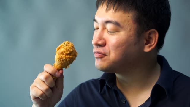 脂肪の男性は、フライド チキンを食べています。幸いにも - unhealthy eating点の映像素材/bロール