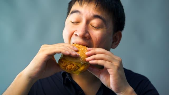 太った男性がハンバーガーを食べています。幸いにも - unhealthy eating点の映像素材/bロール