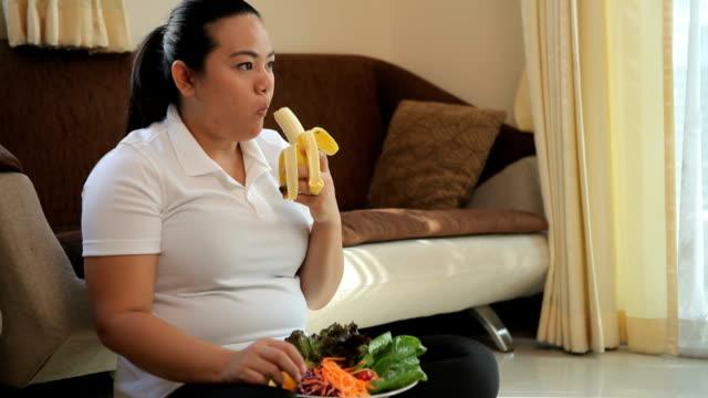 Fat woman eating banana