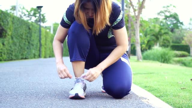 vídeos y material grabado en eventos de stock de mujer gorda corriendo, cordones de los zapatos. - corredora de footing