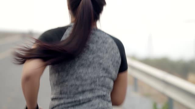 vídeos y material grabado en eventos de stock de gorda joven mujer asiática corriendo o corriendo en el campo de las turbinas eólicas en el concepto de la mañana temprano.saludable. - miembro humano