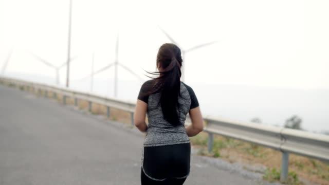 vidéos et rushes de grosse jeune femme asiatique faisant du jogging ou courant au champ d'éolienne dans le concept tôt le matin. - joggeuse