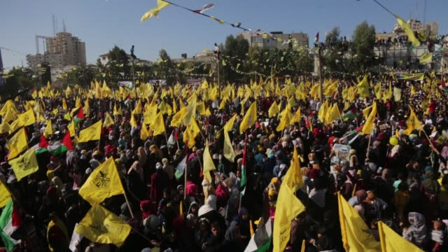 Fatah supporters wave the party flag as they take part in a rally in Gaza City on November 11 2017 marking the death anniversary of late Palestinian...