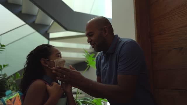 vídeos y material grabado en eventos de stock de padre ajustando máscara protectora de su hija en casa antes de irse a la escuela - padre soltero