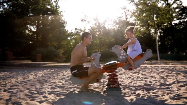 vídeos y material grabado en eventos de stock de padre y una hija joven jugando en un sube y baja - balancín