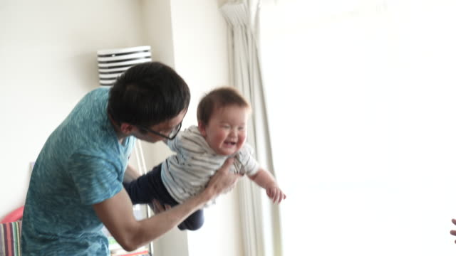 Father and baby boy having fun time in house.