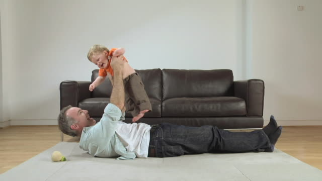 WS Father and baby boy (6-11 months) playing on carpet / London, UK