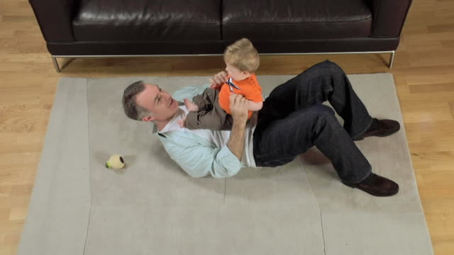 ws father and baby boy (6-11 months) playing on carpet / london, uk  - 6 11 months stock videos & royalty-free footage