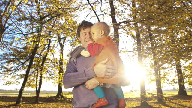 slo mo father and baby enjoying the autumn - modern manhood stock videos & royalty-free footage