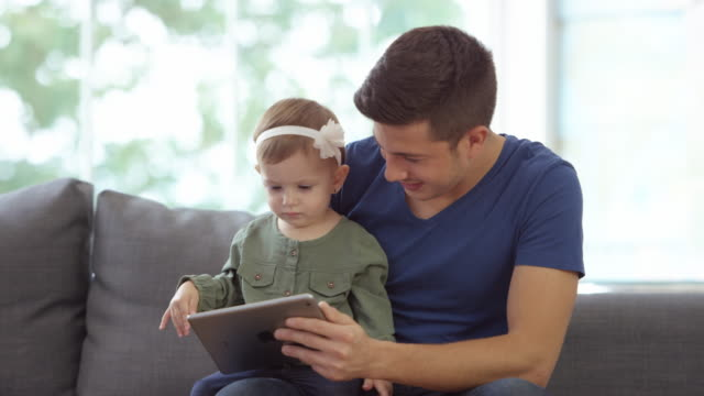father and baby girl using a digital tablet - genderblend stock videos & royalty-free footage