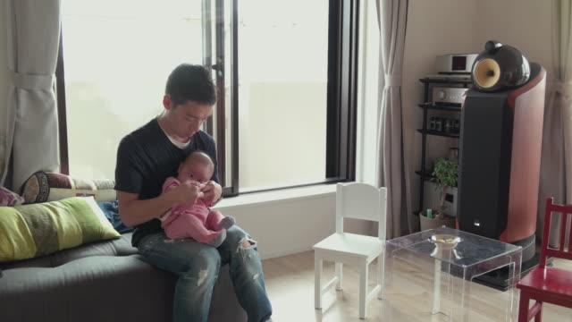 4 k 、父、赤ちゃんのリビングルーム。東京,日本 - リビング点の映像素材/bロール