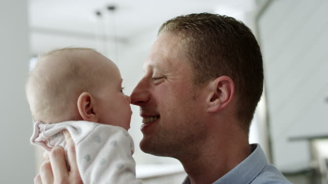 Father and baby kissing like eskimos with their noses