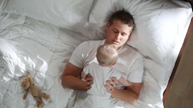 father and baby lying down - オレム点の映像素材/bロール