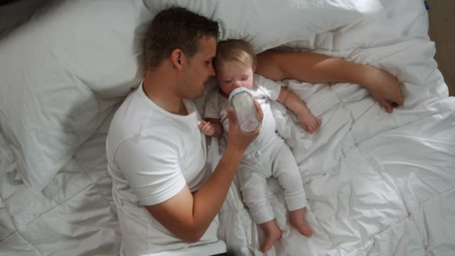 stockvideo's en b-roll-footage met father and baby lying down - zuigfles