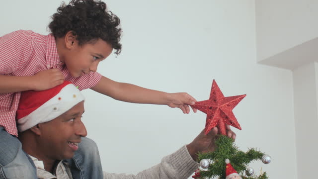 father and child decorating the christmas tree - casual clothing stock videos & royalty-free footage