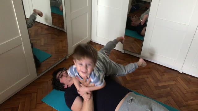 vídeos y material grabado en eventos de stock de padre e hijo haciendo ejercicio en casa - familia con un hijo
