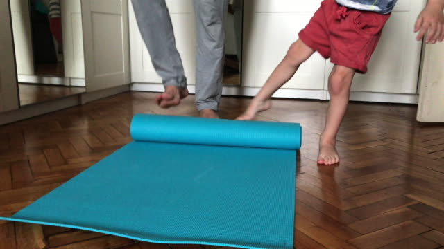 father and child rolling out mat at home preparing for exercising - barefoot stock videos & royalty-free footage