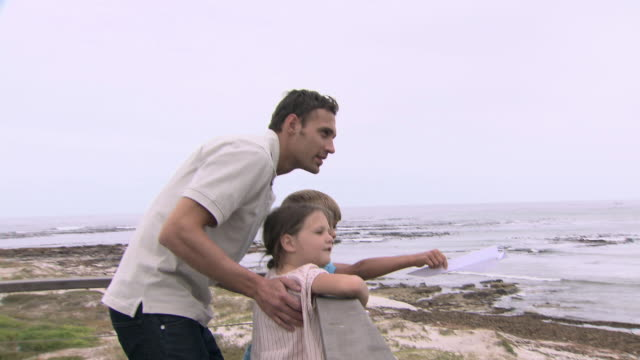 vidéos et rushes de father and children by the sea - hommes d'âge moyen