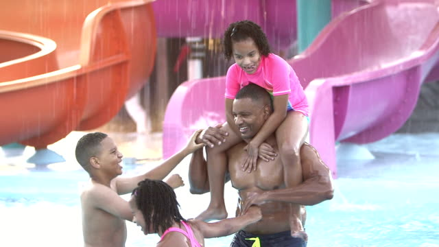 father and children having fun at water park - water park stock videos and b-roll footage