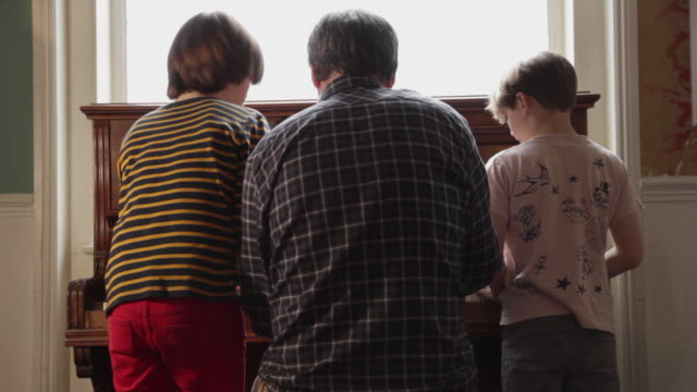 MS Father and children (8-9) playing piano / London, UK