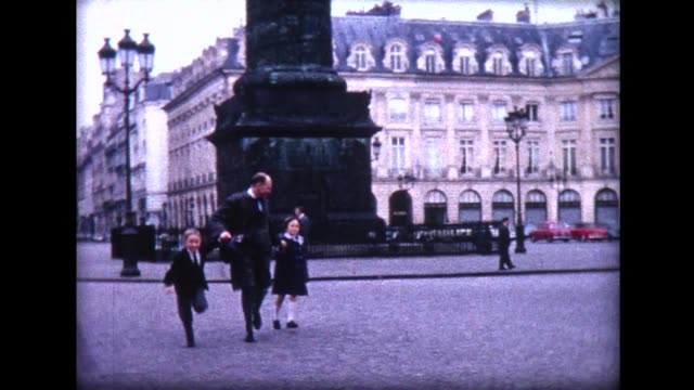 1965 father and children running across Place Vendome