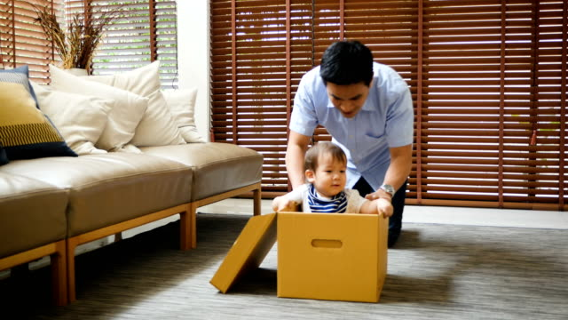 father and cute little son playing with riding in box at home having fun together - baby boys stock videos & royalty-free footage