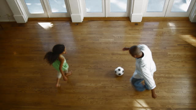 WS HA Father and daughter 12-13) playing with soccer ball in hall / Edmonds, Washington State, USA