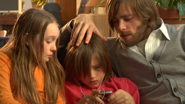 cu, father and daughter (10-11) assisting boy (8-9) listening mp3 player - 10 11 jahre stock-videos und b-roll-filmmaterial