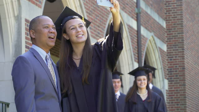 Father and Daughter at Graduation Taking a Selfie